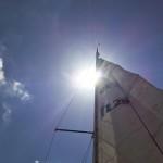 Sun peeking from behind the mainsail.
